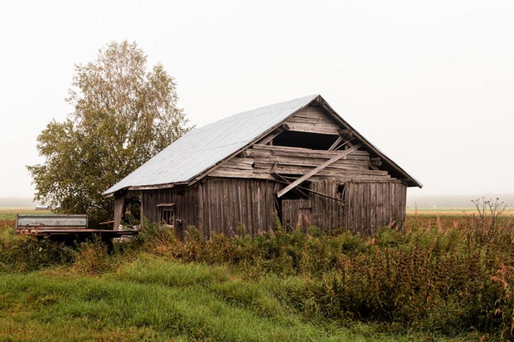 A rusty trailer parked by an old abandoned barn house on the... via Jukka Heinovirta