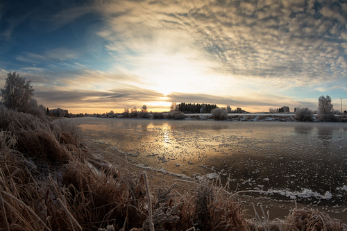 The sun rises over the rive on a cold morning at the rural F... via Jukka Heinovirta
