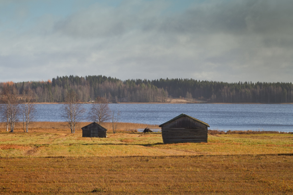 Two old barn houses stand on the autumn fields by a lake in ... via Jukka Heinovirta