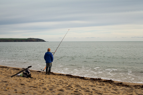 A lonely fisherman standing by his rod at a beach in Cornwal... via Jukka Heinovirta