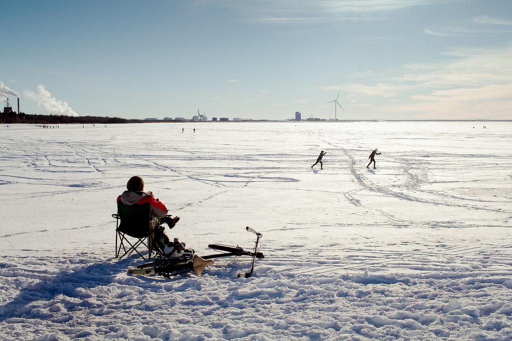 A man is sitting on a beach by a frozen bay. There's a bike ... via Jukka Heinovirta