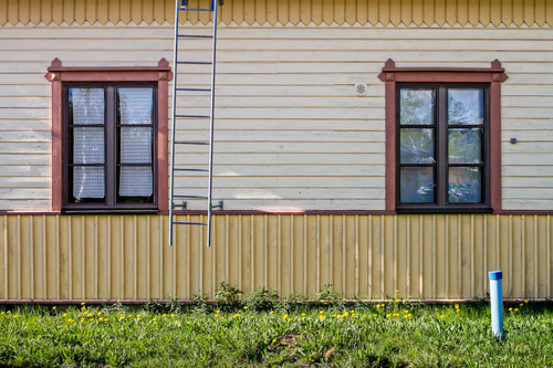 Two windows of an old wooden building. The wall is decorated... via Jukka Heinovirta