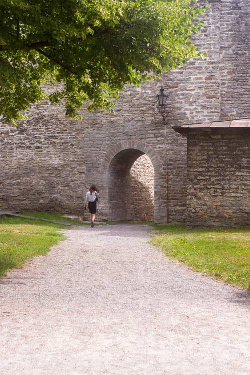 A young woman is walking towards the archway to the medieval... via Jukka Heinovirta