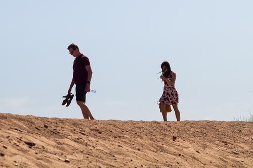 A young couple is walking on the beach, The man is leading t... via Jukka Heinovirta