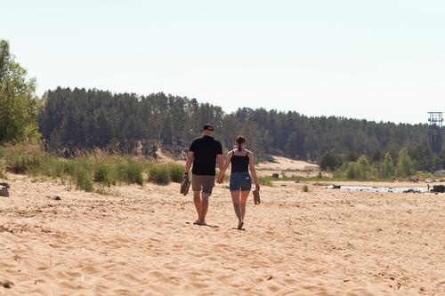 A couple walking on the sand holding their hands. They are a... via Jukka Heinovirta